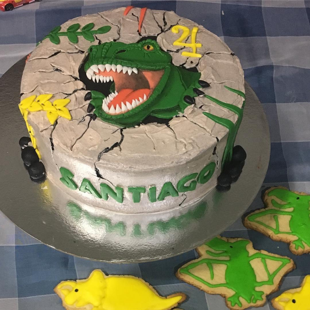 Um belo cliente feliz com seu bolo de dinossauros para seu aniversário n4 1/2 ...